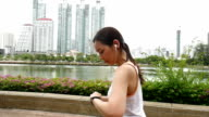 Young woman jogging with smart watch and earbud in city video