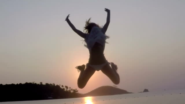 Young woman jumping in slow motion on the beach at sunset video