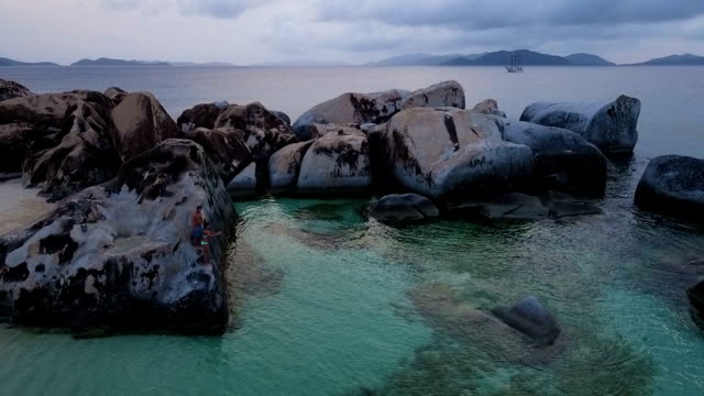 Young woman jumping off a rock in Virgin Gorda video