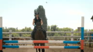 Young woman jumps horse over an obstacle during her training in an arena video