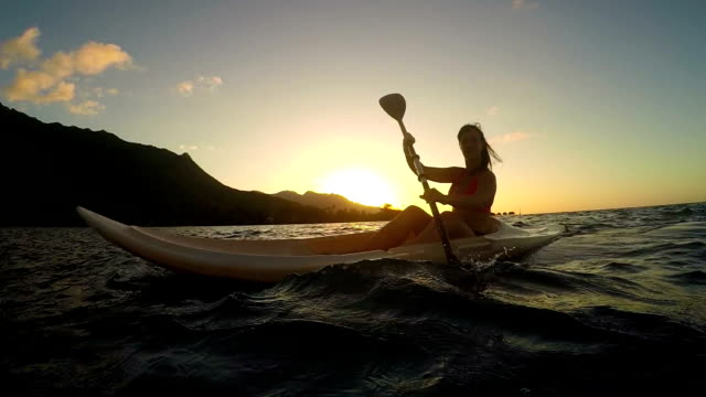 SLOW MOTION: Young woman kayaking on ocean at golden sunset video