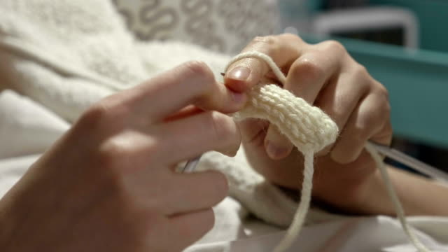 Young woman knits a scarf video