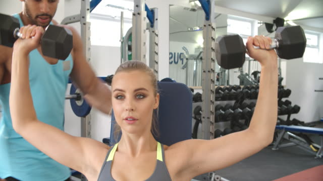 Young woman lifting dumbbells with trainer at a gym video
