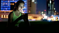Young woman listening music at night outdoors video