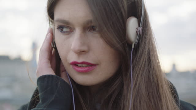 Young woman listening music on roof video