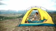 Young woman listening to an mp3 player in a tent video