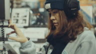 Young woman listening to music in music store video