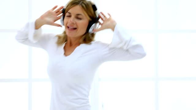 Young woman listening to Music, signing and dancing. video