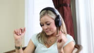 Young woman listening to music video