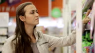 Young woman looking a hygiene goods in the supermarket video