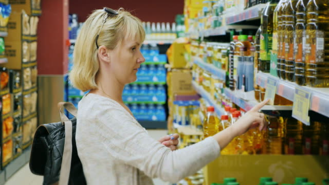 Young woman looking at a bottle of olive or other oil in the supermarket video