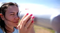 young woman looking through a telescope video