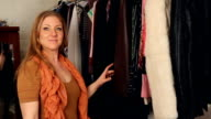 Young woman looking through clothes. video