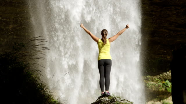 SLOW MOTION: Young woman looking waterfall and raising hands up towards the majestic flowing water in beautiful sunny summer video