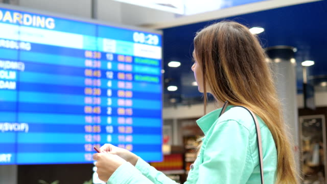Young Woman Looks At The Information Board Of Departures At The Airport. video