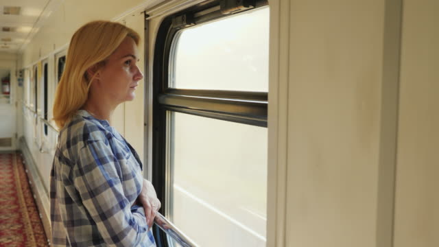 A young woman looks out of the train window. It is in the corridor, the train is moving fast. Dreams and travels video