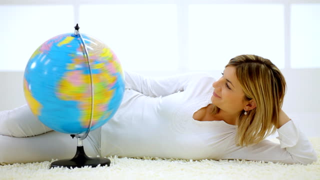 Young woman lying down in room, turning a globe. video