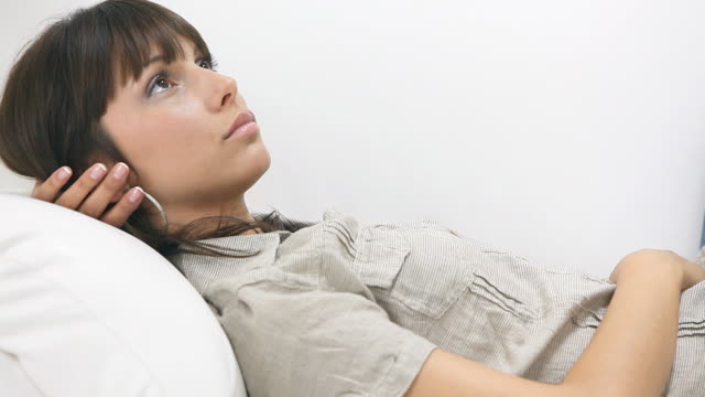 Young woman lying down on sofa and thinking video