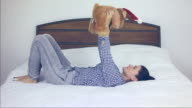 Young woman lying in bed playing with a plush toy. video