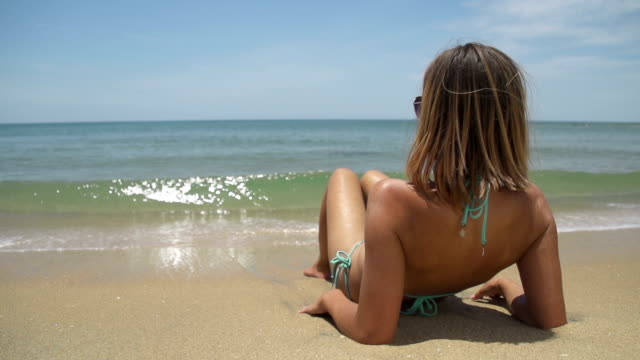SLOW  MOTION: Young woman lying on a exotic beach video