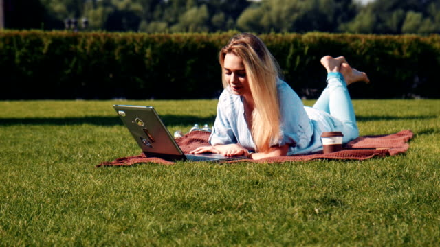 Young woman lying on a lawn using a laptop video