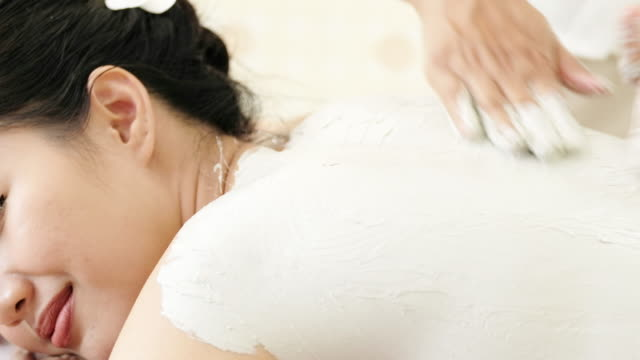Young woman lying on spa bed and massage and clay body mask in spa for relax. video