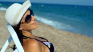 Young woman lying on sunbed, relaxing and enjoying during summer vacation on beach. video