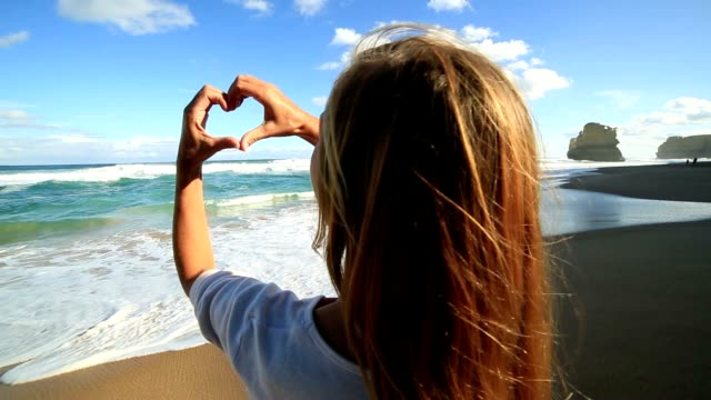 Young woman makes heart shape finger frame on beach video