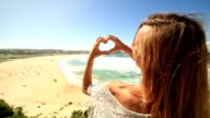 Young woman makes heart shape finger frame on Bondi beach video