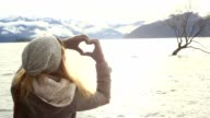 Young woman makes heart shape finger frame on lake Wanaka video