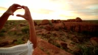 Young woman makes heart shape finger frame to spectacular landscape-sunrise video