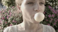 Young woman making a big bubble with a chewing gum video