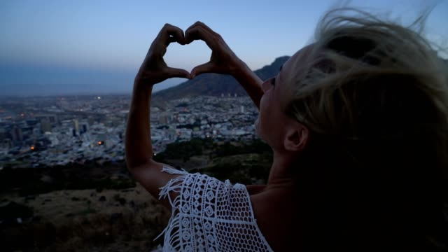 Young woman making heart shape frame in Cape Town at sunrise video