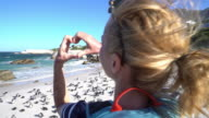Young woman making heart shape on African penguins colony video