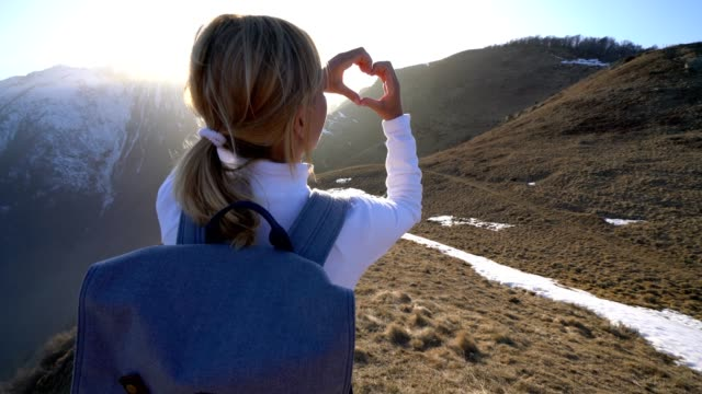 Young woman making heart shape on mountain landscape video