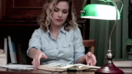 Young woman making last notes, gathering her papers and books from the table and leaving video