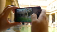 young woman making photos with a smartphone inside a museum, archeological area video