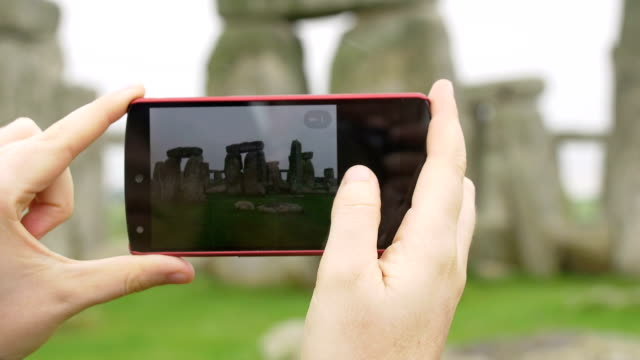 young woman making photos with smartphone to Stonehenge video