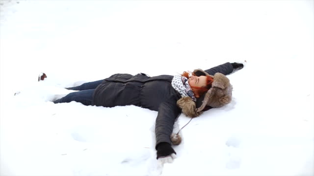 Young woman making Snow angel video