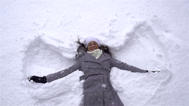 SLOW MOTION: Young woman making snow angels video