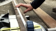 A young woman measuring wood and cutting. video