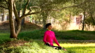 Young woman meditating in the park video