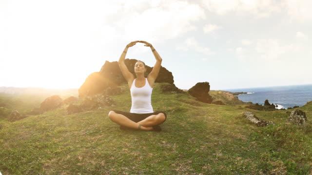 Young woman meditating on Maui coastline video
