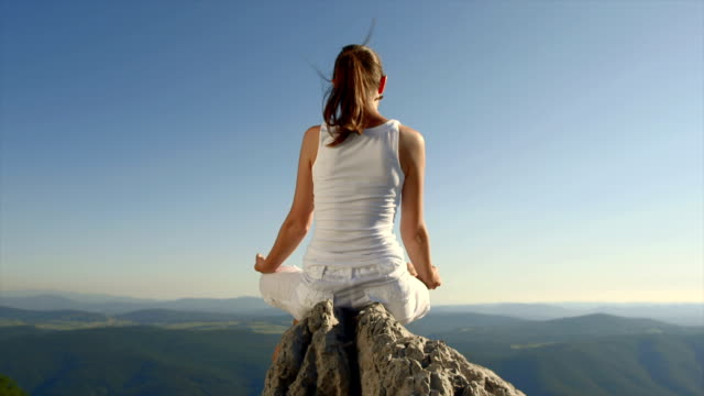 Young Woman Meditating On The Cliff video