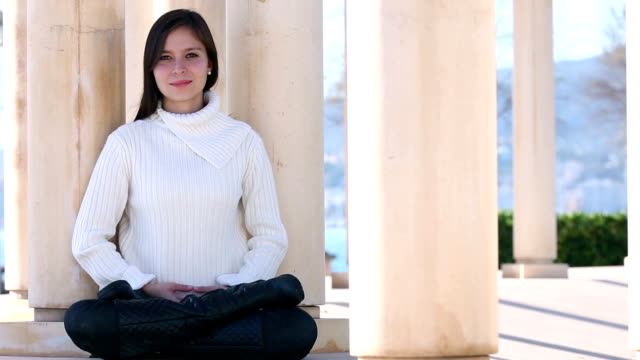Young woman meditating outside video
