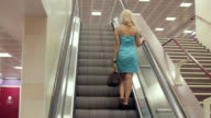 Young woman on a moving escalator video