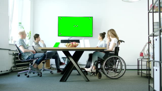 Young woman on a wheelchair and her presenting team discussing with their mentor. Startup company video