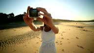 Young woman on beach takes selfie using wearable camera video