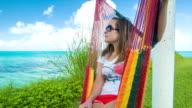 Young Woman on Colorful Hammock in Bermuda Overlooking Tropical Ocean video