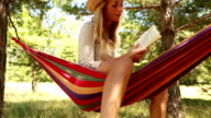 Young woman on hammock in summer reading a book video